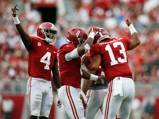 FILE - In this Saturday, Oct. 21, 2017 file photo, Alabama quarterback Tua Tagovailoa celebrates with wide receiver Jerry Jeudy, and running back Josh Jacobs after scoring a touchdown during the second half an NCAA college football game against Tennessee in Tuscaloosa, Ala. Georgia, Alabama, Notre Dame and Clemson are the top four teams in the first College Football Playoff rankings of the season, Tuesday, Oct. 31, 2017. (AP Photo/Brynn Anderson, File)
