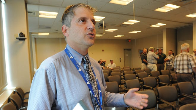 State project engineer Mark Tudor talks after the reading of the bids by the Delaware Department of Transportation contract administration team on Tuesday at the DelDOT headquarters in Dover.