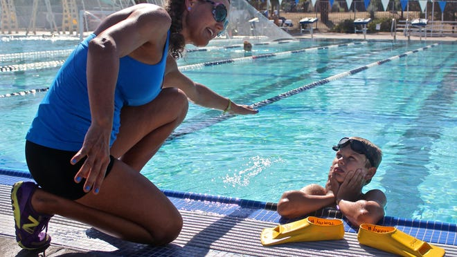 Wendy Ansley, a Kinesiology instructor at the College of the Desert, demonstrates swimming techniques to her ten-year-old son Tommy, Thursday at the Aquatic Center in Palm Desert.