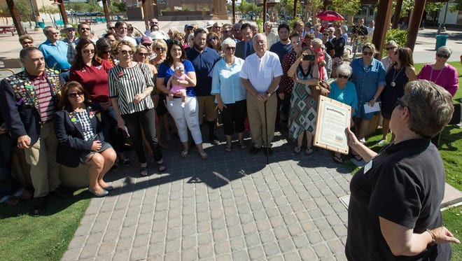 Carrie Hamblen, president and CEO of the Las Cruces Green Chamber of Commerce, reads a proclamation as members of the Ott and Gustafson families, along with friends and others who helped support and raise and donate money for the plaza and splash pad listen, Friday August 24, 2018.