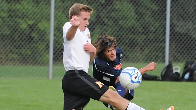 Harrison junior Max Miller works the ball past McCutcheon's Drew Fitzgerald during a rain-plagued matchup Tuesday night.