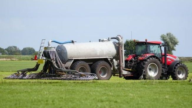 A tractor pulls a tanker that injects manure into the ground.
