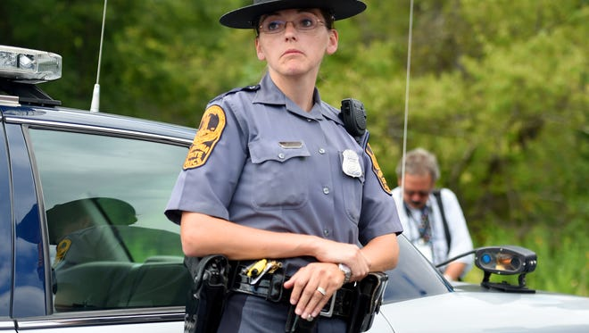 Trooper P.M. Neff of the Virginia State Police answers questions during a press conference near Interstate 66 on Wednesday, August 26, 2015. Neff is the officer who initiated the traffic stop of the vehicle being used by shooting suspect Vester Flanagan.The License Plate Reader that alerted her to the suspects car can been seen on the rear fender of her patrol car.