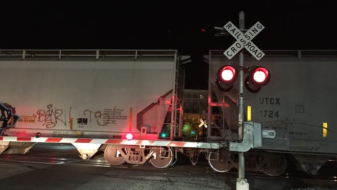 Pedestrians crossed over and under this waiting train Friday night on Main Street in Hattiesburg.