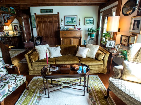 The front sitting room features wingback chairs, an upright piano, antique rugs and artwork.