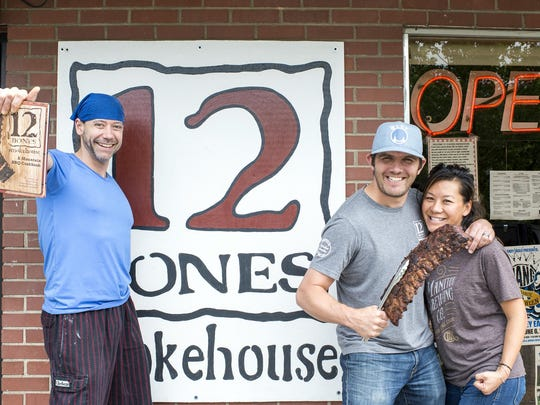 From left, Shane Heavner, Bryan King and Angela King stand outside 12 Bones Smokehouse in the River Arts District to celebrate the 12 Bones cookbook.
