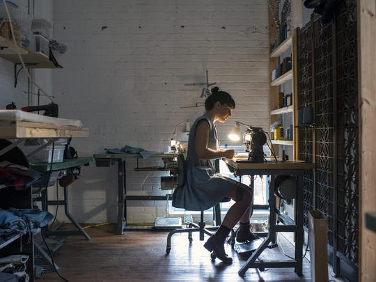 Anna Toth, of Bow and Arrow Apparel, works in her studio at the top of Wedge Studios in the River Arts District. Toth, who specializes in custom-made clothes and denim, also works about one night a week at Wedge Brewery downstairs to supplement her income.