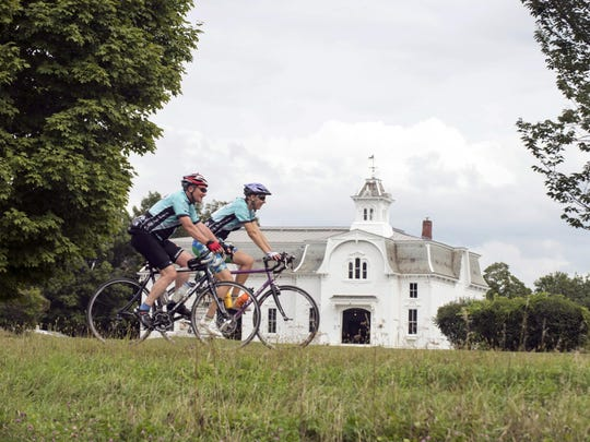 Cyclists ride past the UVM Morgan Horse Farm in Weybridge on the 10th Annual Kelly Brush Century Ride powered by VBT Bicycling and Walking Vacations.