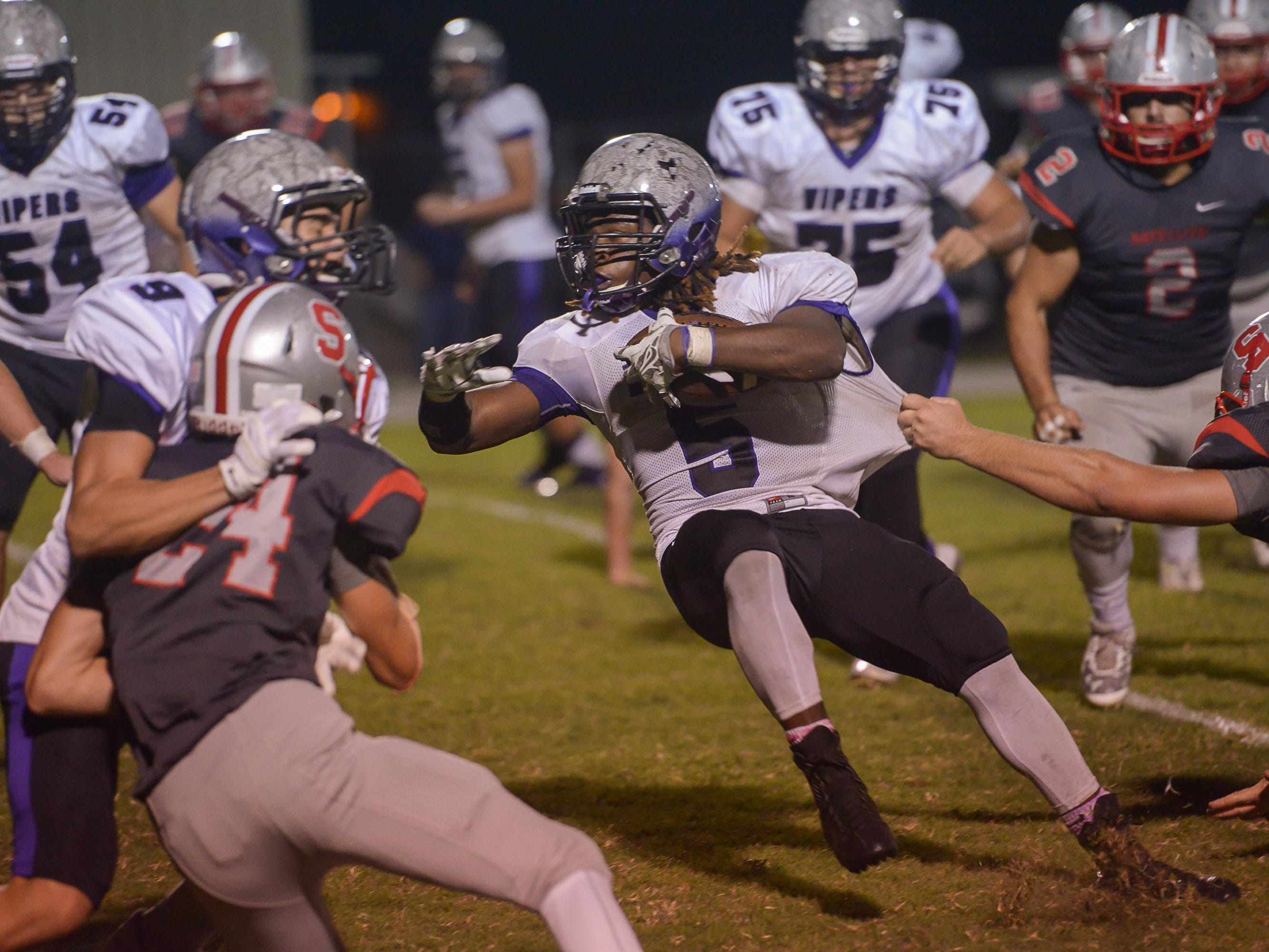 Space Coast's Cornelius Fulton fights for yards against Satellite's defense.