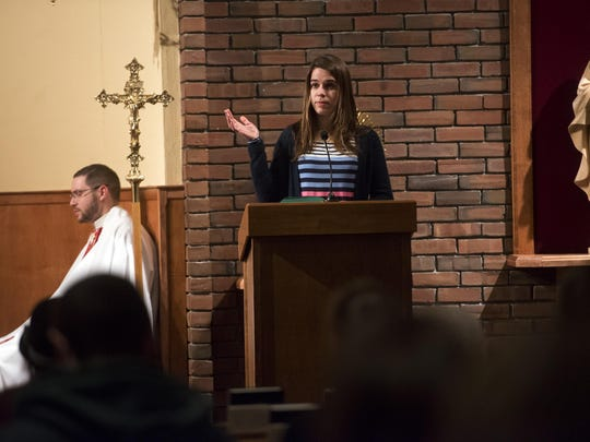 Jenna Lewis, a senior at UVM, reads a prayer on Wednesday night. People gathered for Mass at UVM's Catholic Center after Argentine Jorge Bergoglio was elected Pope Francis on March 13, 2013.
