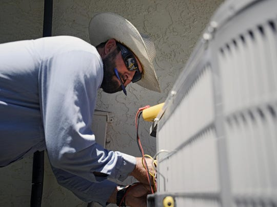 Josh Salow checks an air-conditioning unit at a home in Tempe, Ariz., Thursday. Salow said he fixes three to four units a day in summer months. Parts of the Western U.S. have been getting an early taste of scorching summer heat.