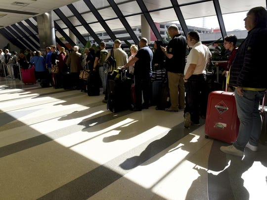 A long line of Delta passengers wait to check in at the Terminal 2 ticket counter at Fort Lauderdale-Hollywood International Airport Sunday morning, Jan. 8, 2017, in Ft. Lauderdale, Fla. A gunman opened fire Friday in a baggage claim area at the Fort Lauderdale international airport, killing five people and wounding eight before he was taken into custody. (Taimy Alvarez/South Florida Sun-Sentinel via AP)