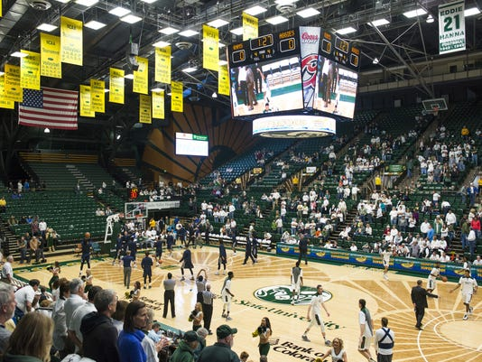 FILE - In this Saturday, Jan. 16, 2016 file photo, the Colorado State men's basketball team warms up on the court at Moby Arena before facing Utah State in an NCAA college basketball game in Fort Collins, Colo. College basketball floors once had simple designs, the only flair usually the addition of color in the lane or at midcourt. Court designs have taken a creative twist over the past few years with schools adding elaborate detail. (Austin Humphreys/The Coloradoan via AP, File)