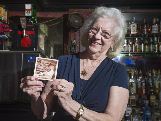 Longtime bartender Melba Murphy, 80, shows a 1967 photo of herself - sporting go-go boots at her first bartending job at the Scenic Hills Lounge - in between taking care of regulars at the Azalea bar in Pensacola on Wednesday, March 15, 2017.