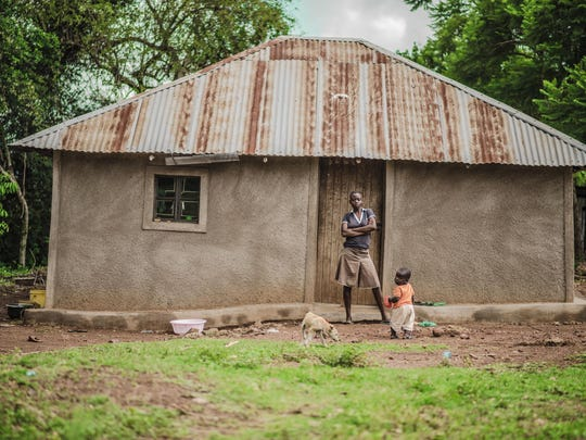 In this April 2017 photo provided by GiveDirectly, GiveDirectly basic income recipient Irine Ogolla poses in front of her home with her son near Lake Victoria in Kenya. The program there distributes $22 a month to residents of the village for the next 12 years — roughly what residents need to buy essentials.