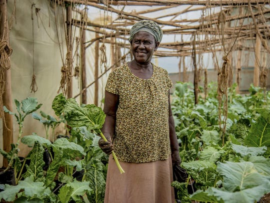 In this April 2017 photo provided by GiveDirectly, GiveDirectly basic income recipient and farmer Benter Were poses for a photo near Lake Victoria in Kenya. The program there distributes $22 a month to residents of the village for the next 12 years — roughly what residents need to buy essentials.