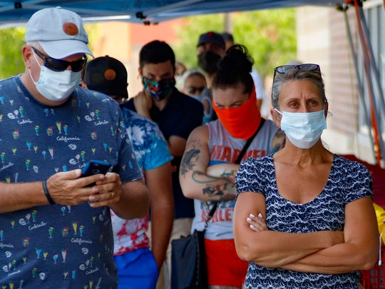 People waiting in line to enter a grocery store wear COVID-19 protective masks Friday in McCandless, Pa.