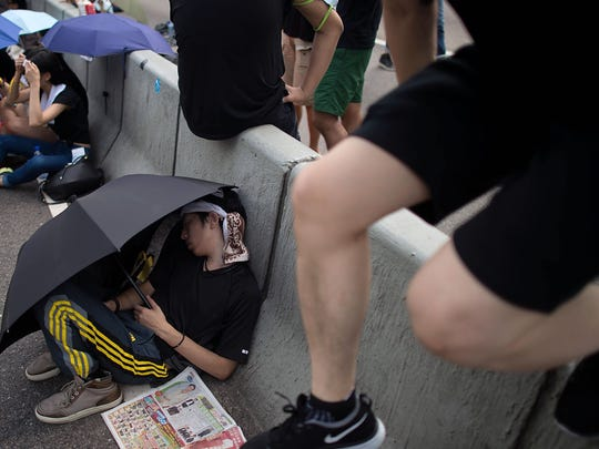 """Protesters sleep on a street outside Hong Kong's government complex on Tuesday, Sept. 30, 2014. Protestors are unhappy with Chinese government's plans to vet candidates for Hong Kong's 2017 elections instead of letting the people choose their own candidates. Some have dubbed the protests the """"Umbrella Revolution"""" because people in the crowd have used umbrellas to block the sun and deflect police pepper spray."""