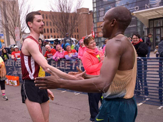 First place finisher for the men in the Rochester Regional Health System Flower City Half Marathon, Patrick Geoghegan, left, greets second place finisher Tisia Kiplangat, right, at the finish line Sunday, April 26, 2015.