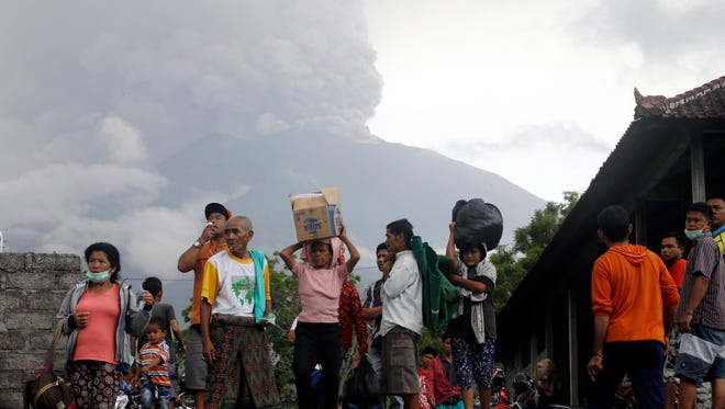 Villagers carry their belongings during an evacuation following the eruption of Mount Agung, seen in the background, in Karangasem, Indonesia on Nov. 26, 2017.