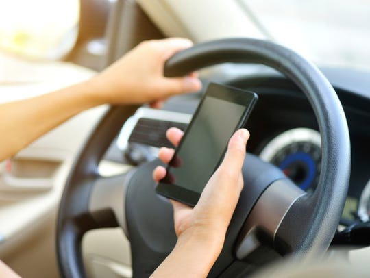 A woman uses her cellphone while driving.