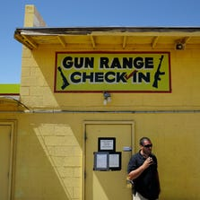 An employee smokes outside of an office for the Last Stop outdoor shooting range Wednesday, Aug. 27, 2014, in White Hills, Ariz. Instructor Charles Vacca was accidentally killed at the range by a 9-year-old with an Uzi submachine gun.