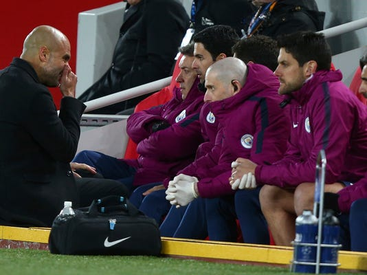 Manchester City coach Josep Guardiola speaks to his coaching staff during the Champions League quarter final first leg soccer match between Liverpool and Manchester City at Anfield stadium in Liverpool, England, Wednesday, April 4, 2018. (AP Photo/Dave Thompson)