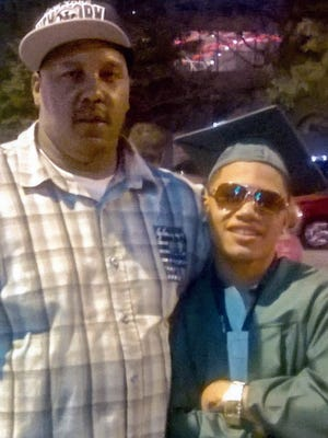 Terrill Thomas, left, stands with his 20-year-old son, also named Terrill, at the son's high school graduation in 2014. The father died in April 2016 while in Milwaukee County Jail.