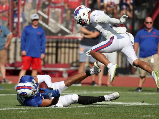Bills tight end Logan Thomas holds onto the ball after a catch as he is defended by Jordan Poyer.