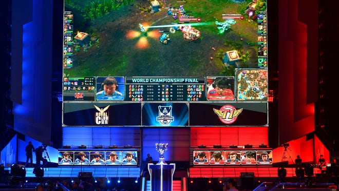 In this Oct. 4, 2013, file photo, the teams of China's Royal Club, left, and South Korea's SK Telecom T1 compete at the League of Legends Season 3 World Championship Final in Los Angeles. Robert Morris University Illinois, a small private university in Chicago, is offering hefty scholarships for players of League of Legends, which has become one of the most popular games for organized team competitions.