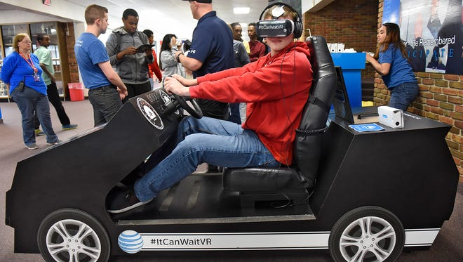 Matthew Tiede takes a turn on a virtual reality simulator Tuesday, May 10, at Apollo High School in St. Cloud. The simulator was designed to show students the dangers of distracted driving.