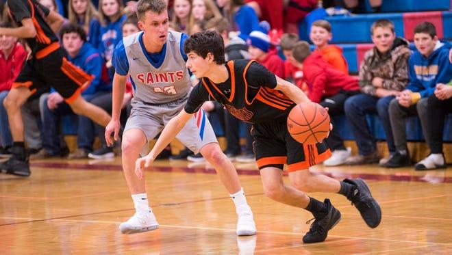 Marine City High School sophomore John Mistretta (right) drives the ball around St. Clair's Scott Selleck during their basketball game at St. Clair High School Dec. 5.
