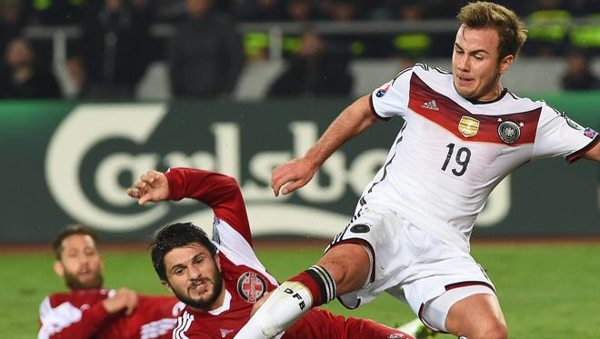 Georgia's George Navalovsky in action against Germany's Mario Goetze during the UEFA EURO 2016 qualifying group D soccer match in Georgia.