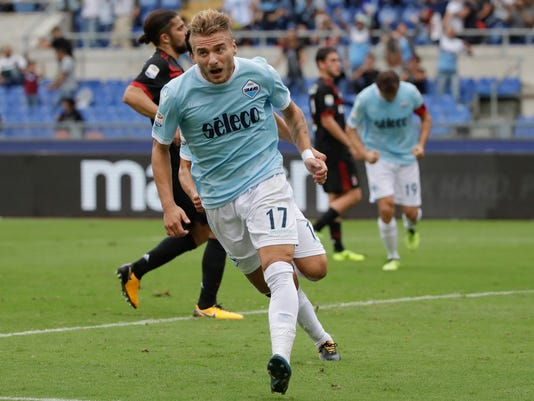 FILE - In this Sunday, Sept. 10, 2017 file photo, Lazio's Ciro Immobile celebrates after scoring during a Serie A soccer match between Lazio and AC Milan, at the Rome Olympic stadium. The first derby since longtime Roma captain Francesco Totti retired is the most anticipated meeting between the capital's two clubs in years. Both Lazio and Roma have had strong starts to the season and sit fourth and fifth, respectively, in the standings with only one point separating them. It will be a matchup between last season's Serie A scoring leader, Roma's Edin Dzeko (29 goals in 37 matches), and this season's scoring leader, Lazio's Ciro Immobile (14 goals in 11 matches). (AP Photo/Alessandra Tarantino, File)