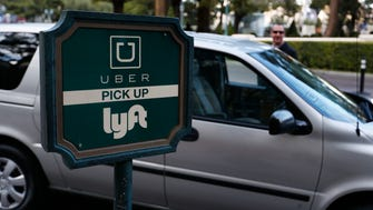 A driver waits to pick up passengers at an Uber and Lyft pick up area in Las Vegas