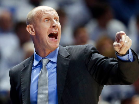 FILE - In this Dec. 2, 2017, file photo, Xavier head coach Chris Mack directs his players during the first half of an NCAA college basketball game against Cincinnati in Cincinnati. According to multiple reports Louisville has hired Xavier's Chris Mack as its new men's basketball coach, hoping he can guide the program back to national contention after a turbulent season in which the Cardinals missed the NCAA Tournament. (AP Photo/John Minchillo, File)