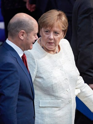 German Finance Minister Olaf Scholz and German Chancellor Angela Merkel talk during a session of the German parliament Bundestag in Berlin, Germany, July 3, 2018.