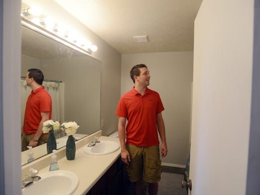 Jackson Rentschler shows off the bathroom he remodeled with new paint, flooring, toilet and shower head, May 30, 2014. Rentschler and his wife purchased a foreclosed home and remodeled it in the past few weeks.