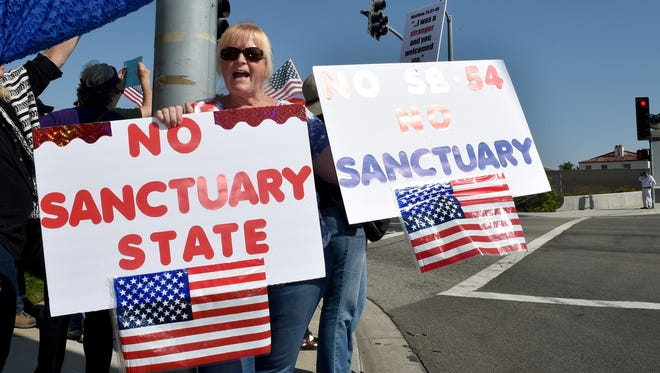 Manuela Walter, an opponent of SB 54, more commonly referred to as the sanctuary state bill, rallies in front of the Camarillo office of California Assemblywoman Jacqui Irwin on Wednesday, where a large number of the bill's proponents gathered on Wednesday.