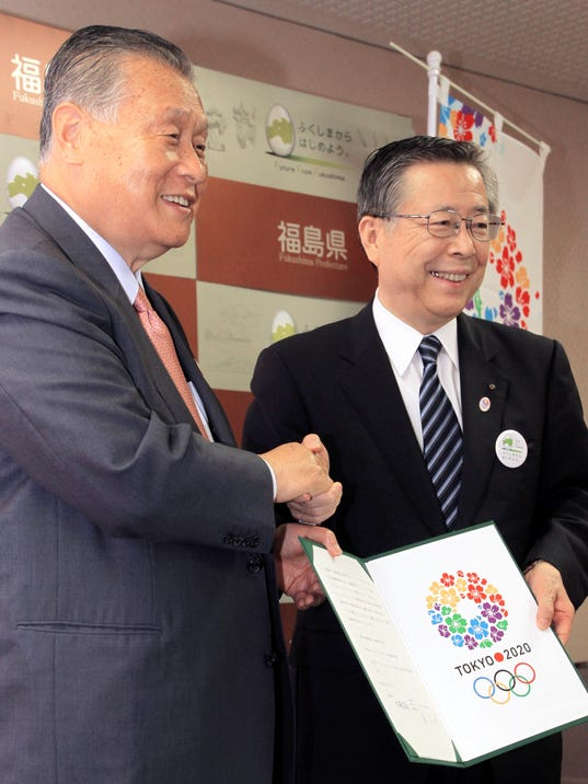 Fukushima Gov. Yuhei Sato, right, poses with Yoshiro Mori, head of the Tokyo Olympics organizing committee, at Fukushima prefectural government's office in Fukushima, northeastern Japan, Tuesday, June 17, 2014. Sato said he wants the Olympic torch to come to the prefecture so the world can see how far the region recovered from the nuclear crisis. Sato made the proposal during a meeting with Mori, former prime minister, who was in Fukushima as part of his tour of northern Japan devastated by the 2011 earthquake and tsunami. (AP Photo/Kyodo News) JAPAN OUT, CREDIT MANDATORY