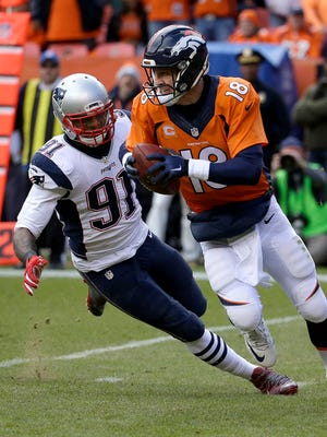 Denver Broncos quarterback Peyton Manning evades a tackle by New England Patriots outside linebacker Jamie Collins (91) during the first half of the NFL football AFC Championship game between the Denver Broncos and the New England Patriots oin Sunday in Denver.