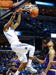 University of Memphis forward Jimario Rivers (left) completes a slam dunk in front of East Carolina University defender Andre Washington (right) on his way to a game-high 15 points at the FedExForum.