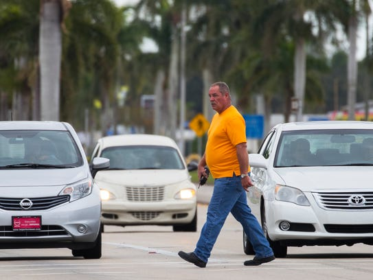 Lee County Sheriff Sgt. Dan Leffin, a member of the traffic unit, crosses Palm Beach Boulevard at the intersection with Ortiz Avenue on Tuesday morning, while conducting an undercover operation enforcing pedestrian and bicycle safety. The undercover operation is part of a six-month program to make the county's streets safer for drivers, bikers and pedestrians.