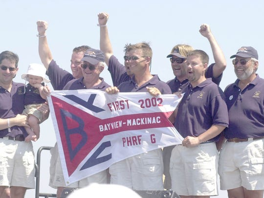 Jewell crew members — including Doug Touma with his son Drew and Pat Hoy, fourth from the right — celebrate  aboard the Santana 35 that won PHRF G Class in the 2002 Port Huron-to-Mackinac Island Sailboat Race.
