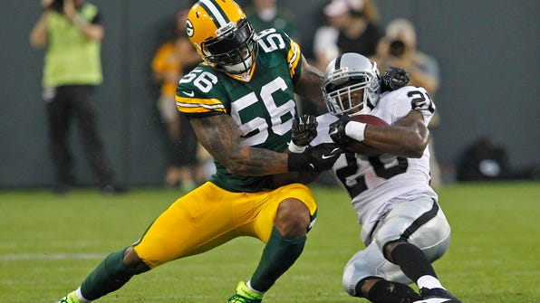 FILE - In this Aug. 22, 2014, file photo, Green Bay Packers defensive end Julius Peppers hits Oakland Raiders running back Darren McFadden during an NFL preseason football game in Green Bay, Wis. After eight years, Peppers is returning home to play for the Carolina Panthers. The Panthers agreed to terms on a contract Friday, March 10, 2017, with Peppers, their all-time sack leader, according to a person familiar with the negotiations. The person spoke to The Associated Press on Friday on condition of anonymity because the move can't officially be announced until later in the day. (AP Photo/Matt Ludtke, File)