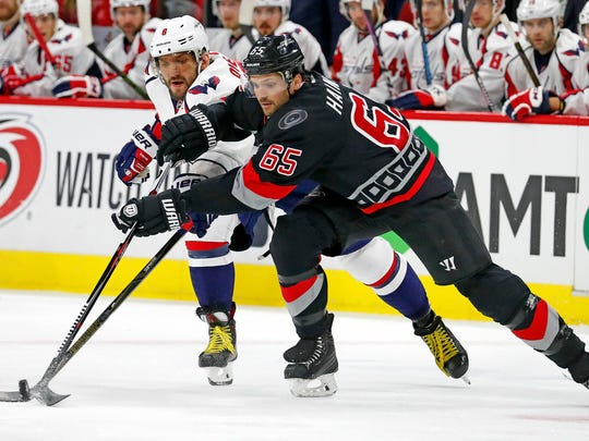 Carolina Hurricanes defenseman Ron Hainsey, right, tangles with the Washington Capitals' Alex Ovechkin on Nov. 12, 2016, in Raleigh, N.C.