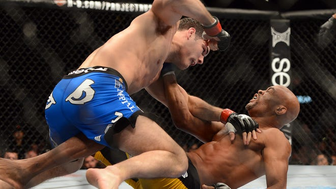 Chris Weidman punches Anderson Silva during their UFC middleweight championship bout at the MGM Grand Garden Arena on Dec. 28. Weidman won when Silva broke his leg.