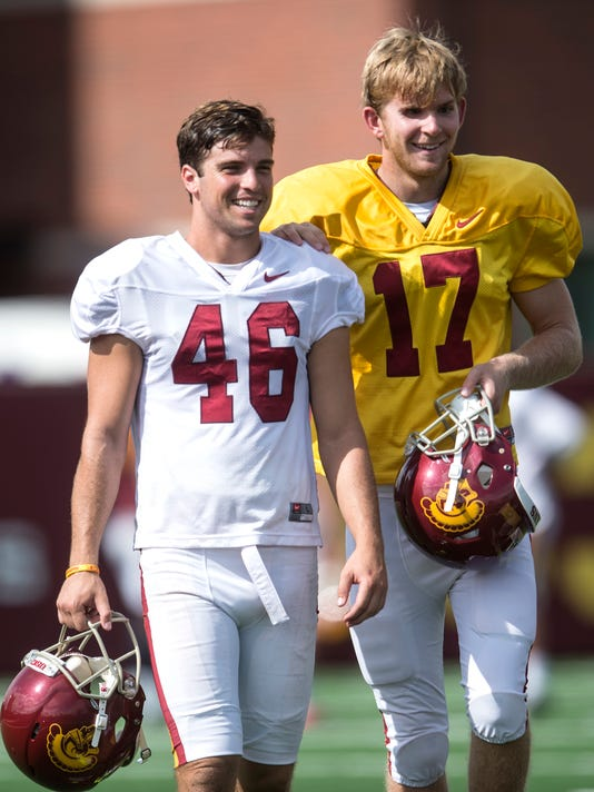 FILE - In this Sept. 15, 2015, file photo, Reid Budrovich, left, guides teammate Jake Olson, through the field during Southern California football practice in Los Angeles. Olson completed two field goal snaps in the Trojans' spring game Saturday, April 16, 2016. Olson got a standing ovation at the Coliseum before he participated in USC's final workout of the spring. (Ed Crisostomo/The Orange County Register via AP)