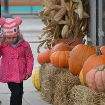 Claire Hoffman holds her dad's hand as they walk down 8th Street during Harvest Fest.