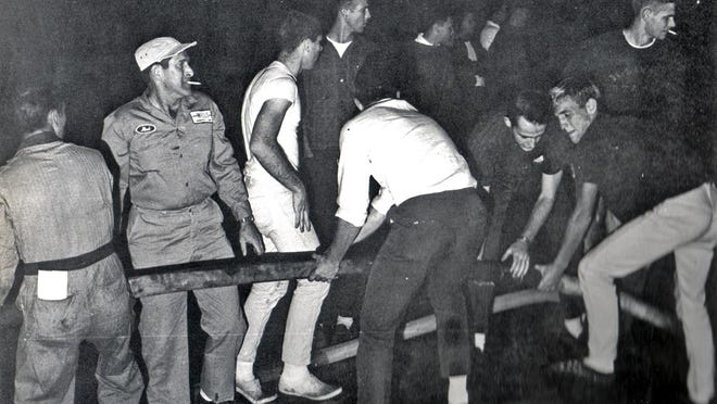 Monmouth College students help man a fire hose at one of three raging fires that were set in Monmouth on the night of Oct. 14, 1963.